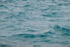 Fotoclose-up van mooie duidelijke turkooise overzeese oceaanwaterspiegel met rimpelingen lage golven op zeegezichtachtergrond Royalty-vrije Stock Foto's