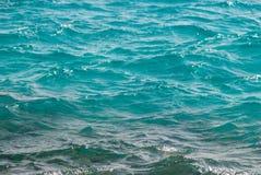 Fotoclose-up van mooie duidelijke turkooise overzeese oceaanwaterspiegel met rimpelingen lage golven op zeegezichtachtergrond Royalty-vrije Stock Afbeelding
