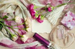 Fotocomposizione in uno stile d'annata delicato nei colori pastelli Le rose rosa del tè si trovano su una sciarpa di seta, circon Immagini Stock
