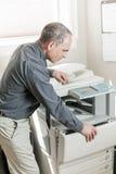 Fotocopiadora de la abertura del hombre en oficina Fotos de archivo libres de regalías