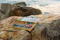 Fotoet använda vatten-färg målarfärg-asken, målarfärgbrushon, borstar på stenar nära havskusten Arkivfoton