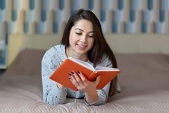 Fotoet av den avkopplade Caucasian kvinnliga modellen läser den röda boken, har försiktigt leende på framsida, tycker om den bra  arkivbild