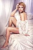 Fotoet av den blonda härliga kvinnan som in poserar, snör åt kläder på säng Royaltyfri Bild