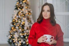 Fotoet av den fundersamma kvinnliga modellen bär den röda tröjan, dricker te, har mörkt hår, beskådar om något, står i spaciouss  royaltyfri foto