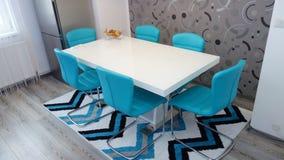 Fotoet av den mitt- formatköklägenheten i turkosfärger, piskar modern och minimalist seater, den vita äta middag tabellen för sex Royaltyfri Bild