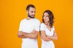Fotoet av den olyckliga mannen och kvinnan grälar in att stå tillbaka som ska dras tillbaka med vikta armar, isolerat över gul ba arkivbilder