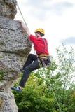 Fotoet av den sportiga mannen i hjälm som över bestiger, vaggar mot bakgrund av gröna träd Royaltyfri Foto