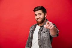 Fotoet av den stiliga gladlynta man30-tal i jeans klår upp att le och p Royaltyfri Fotografi