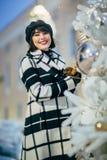 Fotoet av den unga brunetten går på bredvid dekorerad vit gran utomhus royaltyfria bilder