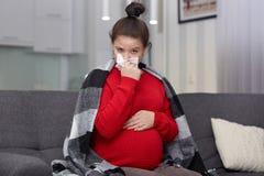 Fotoet av den unga gravida kvinnan har den säsongsbetonade sjukdomen, fångade kallt under vinter, använder näsduken, försöker att fotografering för bildbyråer