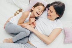 Fotoet av det förtjusande småbarnet och hennes moder har gyckel tillsammans I arkivfoton