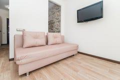 Fotoet av det ljusa rummet med en soffa och TV:N royaltyfri foto