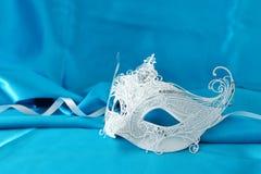 Fotoet av elegant och delikat vit snör åt den venetian maskeringen över ljus turkossilkebakgrund royaltyfria bilder