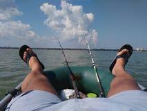 Fotoet av en fiskare som har, vilar på en fiska tur i ett fartyg arkivbild