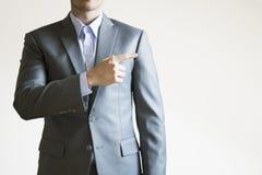 Fotoet av en man i grå färger passar att peka på tomt utrymme bredvid honom Royaltyfria Foton