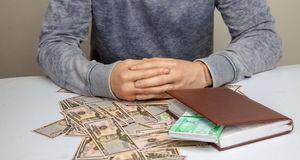 Fotoet av en man sitter på en tabell som överhopas med pengar Royaltyfria Foton