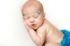 Fotoet av ett nyfött behandla som ett barn krullat sova upp på en filt Arkivbild