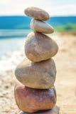 Fotoet av fem stenar balanserade överst av de på en strand Arkivbild