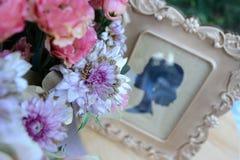 Fotoet av gästtabellen med lilor blommar med fotoramen Arkivfoton