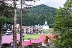 Fotoet av gräsplan når en höjdpunkt, och en touristic by med blått kyrktar i fagarasberg Royaltyfri Fotografi