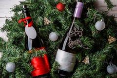 Fotoet av granen förgrena sig med två flaskor av vin, tomt hälsningkort Arkivbild