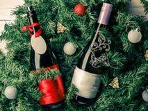 Fotoet av granen förgrena sig med två flaskor av vin, tomt hälsningkort Fotografering för Bildbyråer