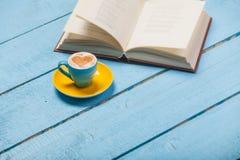 Fotoet av koppen kaffe och den öppnade boken på de underbara blåtten uppvaktar Arkivbilder