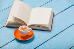 Fotoet av koppen kaffe och den öppnade boken på de underbara blåtten uppvaktar Royaltyfri Bild