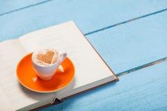 Fotoet av koppen kaffe och den öppnade boken på de underbara blåtten uppvaktar Royaltyfria Bilder