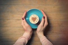 Fotoet av kvinnlign räcker den hållande koppen kaffe på den underbara broen Royaltyfri Foto
