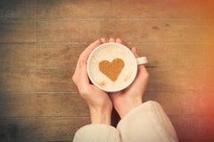 Fotoet av kvinnlign räcker den hållande koppen kaffe på den underbara broen Arkivfoto