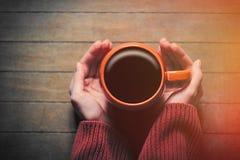 Fotoet av kvinnlign räcker den hållande koppen kaffe på den underbara broen Arkivbilder