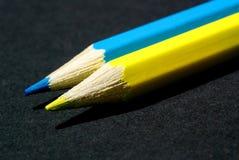 Fotoet av vässade guling och blått ritar närbilden som i rad ligger på en mörk bakgrund fotografering för bildbyråer