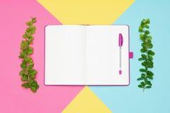 Fotoet för den bästa sikten av kontorsskrivbordet med den öppna notepaden för mellanrumsåtlöje upp och en penna på pastell färgad arkivfoto