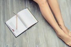 Fotoet för den bästa sikten av kvinna` s lägger benen på ryggen på trägolv med den öppnade dagboken arkivbilder