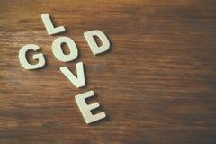 Fotoet för den selektiva fokusen av ordförälskelsen är guden som göras med kvarterträbokstäver på träbakgrund religion för bokbeg royaltyfri bild