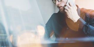 Fotoet uppsökte den vuxna hipsteren som arbetar på det moderna stads- kafét Man som bär den svarta skjortan och talar den moderna Royaltyfri Bild