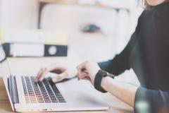 Fotoflicka som arbetar den moderna bärbara datorn i studiovind Kvinna som ser den generiska designen Smartwatch för skärm Kontoch Royaltyfri Bild
