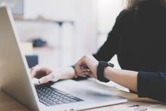 Fotoflicka som arbetar den moderna bärbara datorn i studiovind Kvinna som ser den generiska designen Smartwatch för skärm Chef Wo Arkivfoton