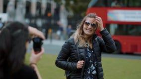 Fotofors i London - den unga kvinnan poserar för den perfekta bilden i ultrarapid arkivfilmer