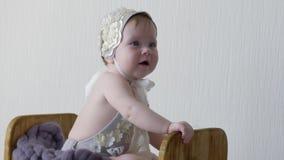 Fotoforsen av en begynnande flicka i huvudbonad och klänning sitter, i träask och att posera på kamera lager videofilmer