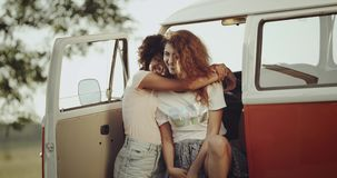 Fotogeniska flickor för lockigt hår med perfekt vit smilie, har en bra tid tillsammans i ett busssammanträde utanför att krama va lager videofilmer