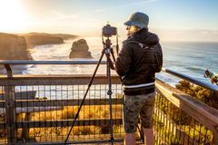 Fotograaf aan de Twaalf Apostelen bij zonsondergang stock afbeeldingen