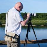 Fotograaf bij een meer stock afbeelding