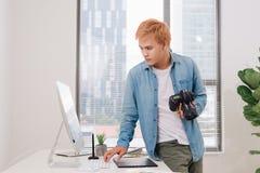 Fotograaf die bij bureau in modern bureau werken stock foto