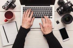Fotograaf die laptop op werkplaats met behulp van stock foto