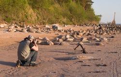 Fotograaf die schot op de kust met oude vuurtoren maken Royalty-vrije Stock Foto's