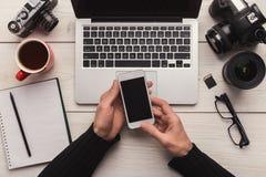Fotograaf die smartphone op werkplaats gebruiken stock afbeeldingen