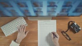 Fotograaf die vertoning en toetsenbord gebruiken om foto's van computervertoning te selecteren Hoogste mening stock footage