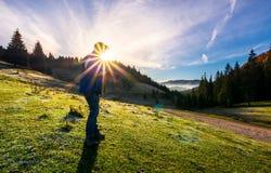 Fotograaf die in zonnestraal mistig landschap schieten stock foto